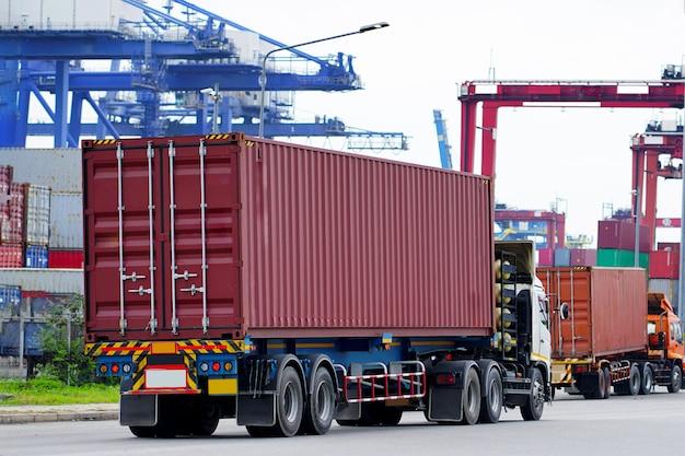 Lading rode containervrachtwagen in scheepshaven logistiek. transportindustrie in havenbedrijf. import, export logistiek industrieel Premium Foto