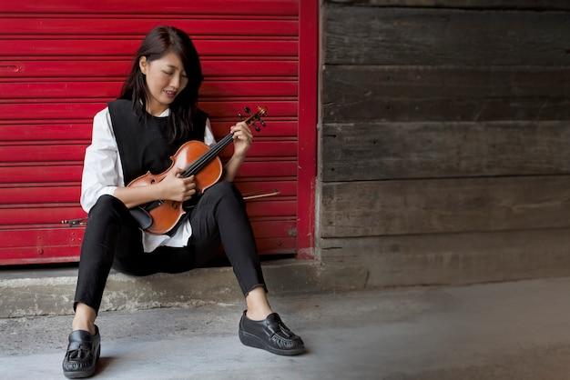 Lady gebruikt de vinger om de strijkers van viool te plukken, the pizzicato technique Premium Foto