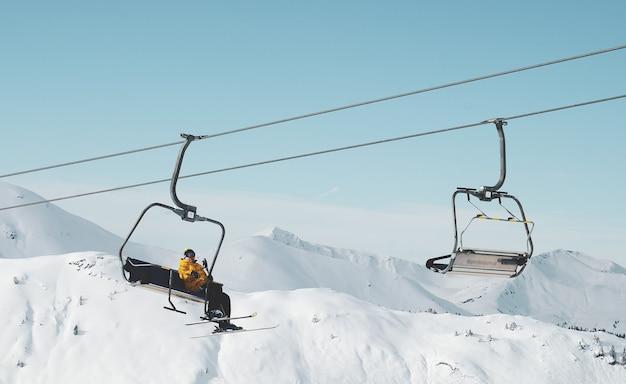 Lage die hoek van een persoon is ontsproten die op een kabelbaan in een besneeuwde berg zit Gratis Foto