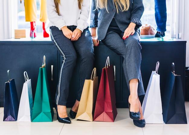 Lage gedeelte van twee vrouwelijke zitten in de winkel met kleurrijke boodschappentassen Gratis Foto