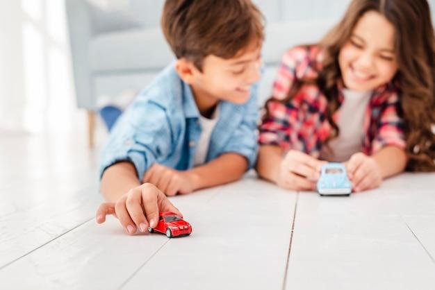 Lage hoek broers en zussen op vloer spelen met speelgoed Gratis Foto