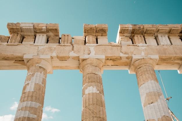 Lage hoek die van de kolommen van het pantheon van de akropolis in athene, griekenland onder de hemel is ontsproten Gratis Foto