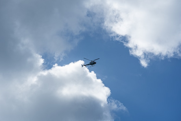 Lage hoek die van een helikopter in de bewolkte hemel is ontsproten Gratis Foto