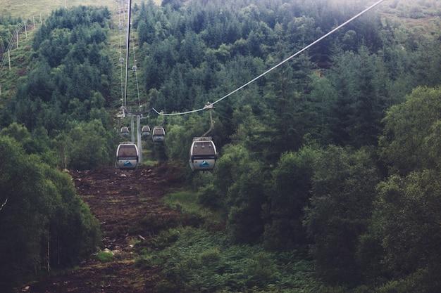 Lage hoek die van een kabelbaan in het midden van een groen bergachtig landschap is ontsproten Gratis Foto