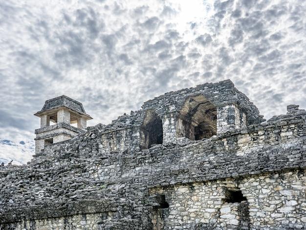 Lage hoek die van een oud gebouw onder een bewolkte hemel overdag is ontsproten Gratis Foto
