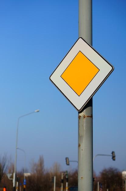 Lage hoek die van een prioriteitsverkeersbord is ontsproten onder een duidelijke blauwe hemel Gratis Foto