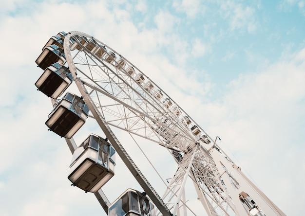 Lage hoek die van een reuzenrad met bewolkte blauwe hemel is ontsproten Gratis Foto