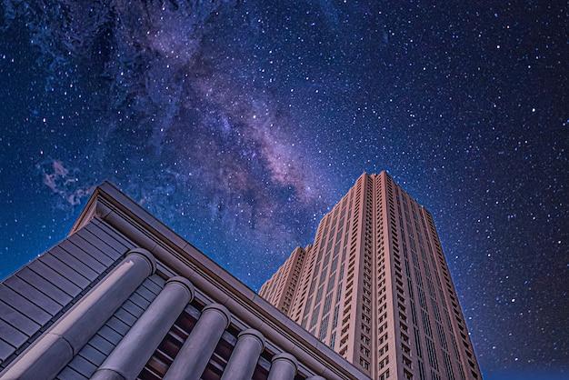 Lage hoek die van hoge gebouwen onder een sterrige nachthemel is ontsproten Gratis Foto