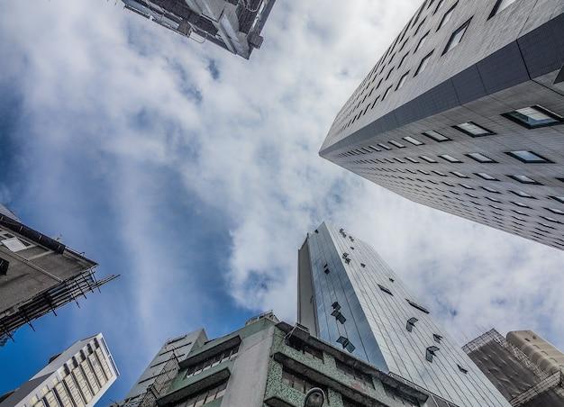 Lage hoek die van hoge woongebouwen onder de bewolkte hemel is ontsproten Gratis Foto