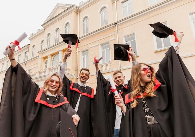 Lage hoek gelukkig afgestudeerde studenten Premium Foto