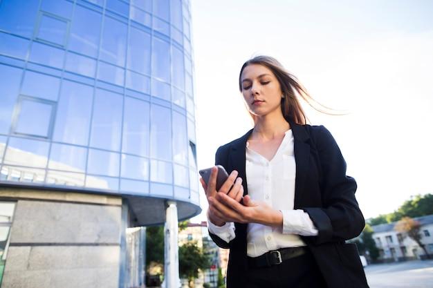 Lage hoek geschotene vrouw die een telefoon met behulp van Gratis Foto