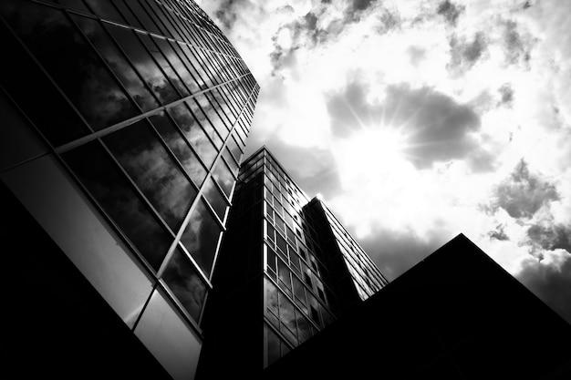 Lage hoek grijstinten shot van zakelijke gebouwen met een bewolkte hemel op de achtergrond Gratis Foto