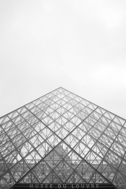 Lage hoek grijstinten van het louvremuseum onder een bewolkte hemel in parijs in frankrijk Gratis Foto