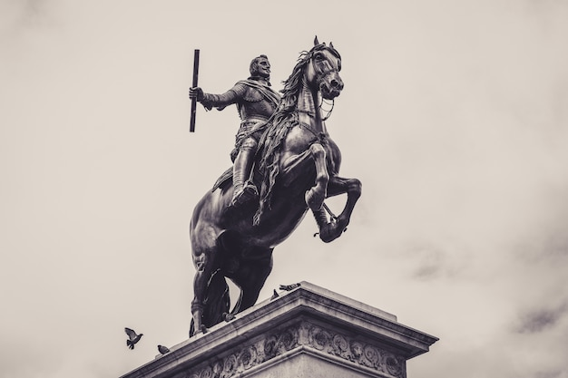 Lage hoek grijswaarden shot van een standbeeld voor het koninklijk paleis van madrid Gratis Foto