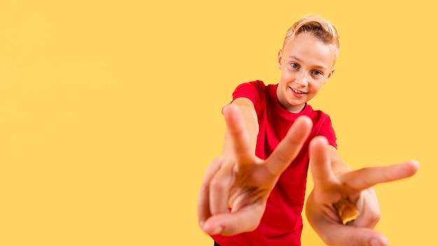 Lage hoek jonge jongen die vredesteken toont Gratis Foto