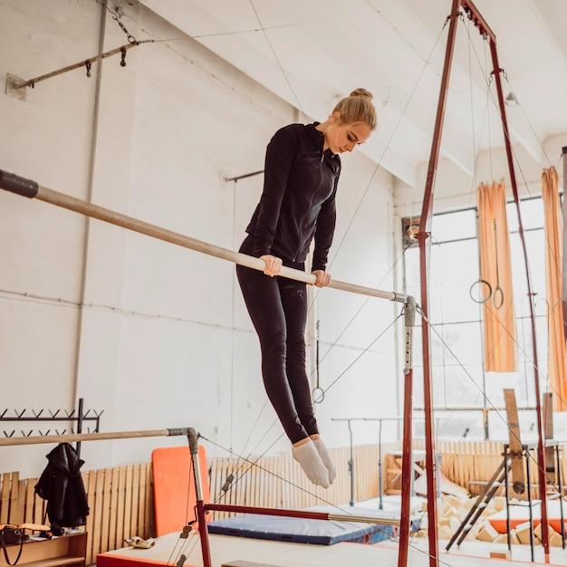 Lage hoek jonge vrouw training voor gymnastiek kampioenschap Gratis Foto
