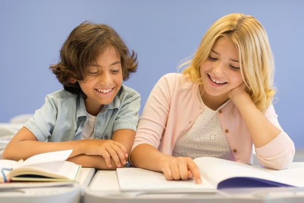 Lage hoek jongen en meisje lezen Gratis Foto
