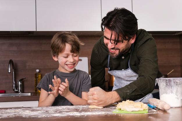 Lage hoek kleine jongen met vader rollend deeg Gratis Foto