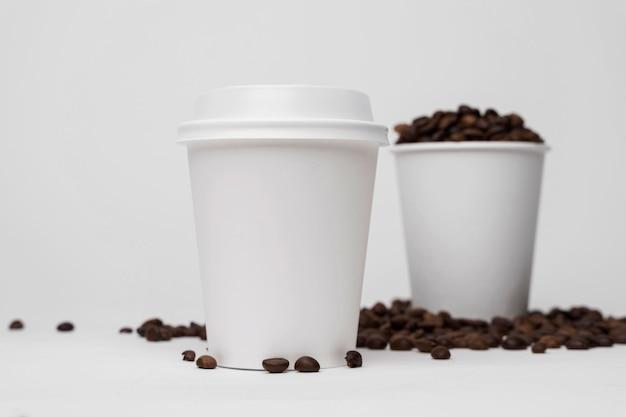 Lage hoek koffiekopjes en bonen Gratis Foto