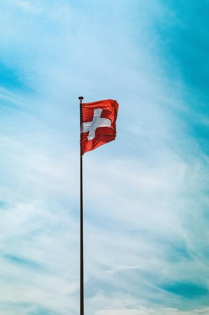 Lage hoek schot van de vlag van zwitserland op een paal onder de adembenemende bewolkte hemel Gratis Foto