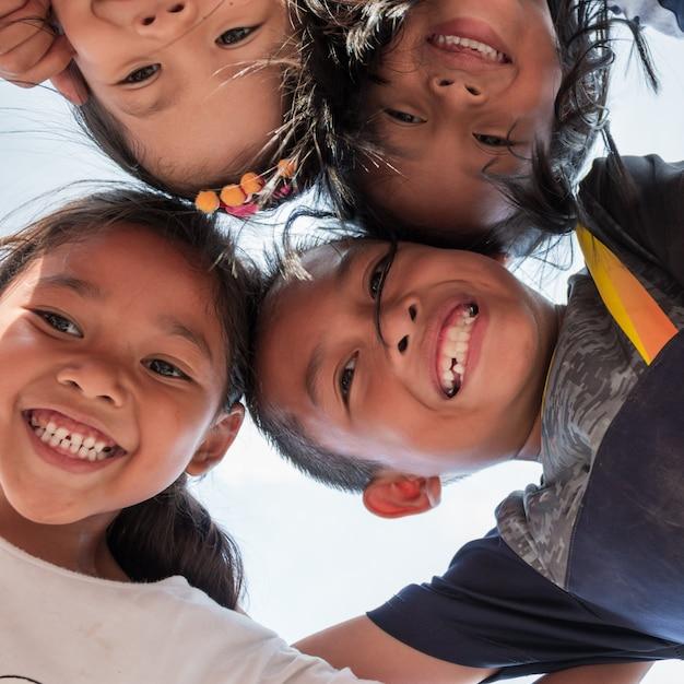 Lage hoek schot van opgewonden kinderen staan in cirkel knuffelen camera kijken naar samen spelen, team van lachende kinderen omhelzen samen in een cirkel. portret van jonge jongen en meisjes die camera bekijken Premium Foto