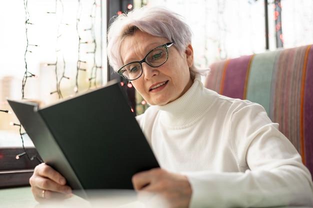 Lage hoek senior vrouw lezen Gratis Foto