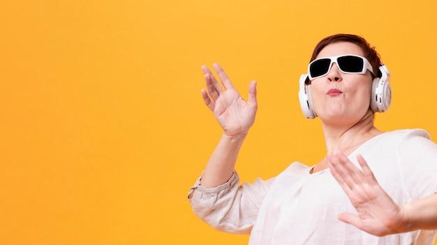 Lage hoek senior vrouw luisteren muziek en dansen Gratis Foto