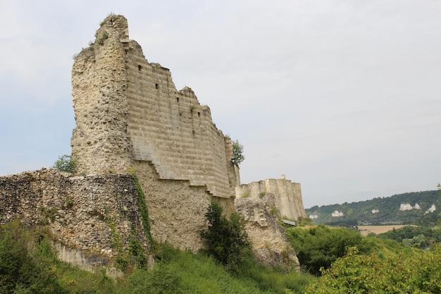 Lage hoek shot van de ruïnes van een kasteel in frankrijk met de grijze lucht op de achtergrond Gratis Foto