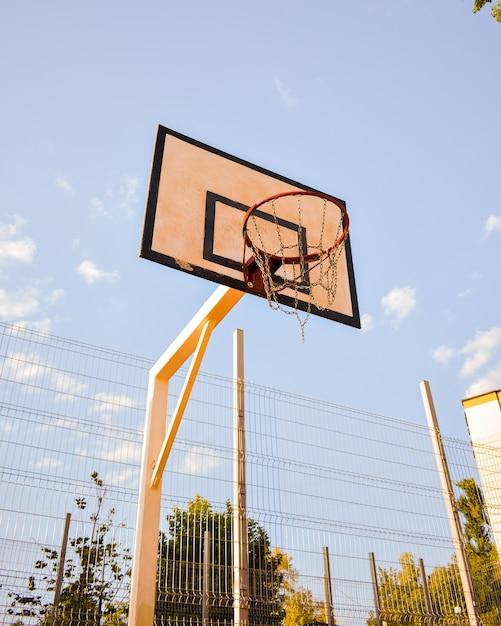 Lage hoek shot van een basketbalring met ketting net tegen een blauwe bewolkte hemel Gratis Foto