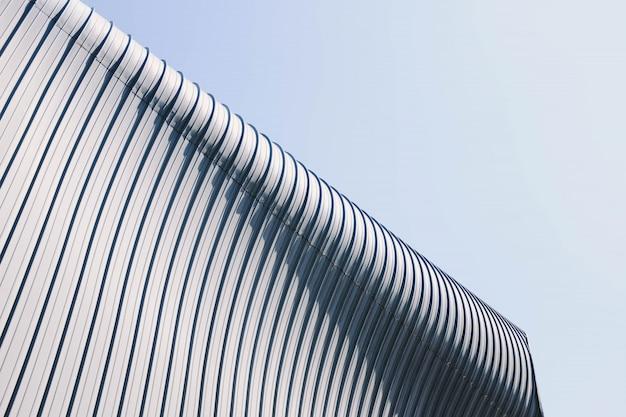 Lage hoek shot van een grijs en wit dak van het gebouw met interessante texturen onder de blauwe hemel Gratis Foto