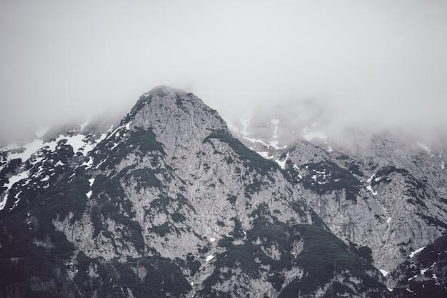 Lage hoek shot van een hoge rotsachtige berg bedekt met dikke mist Gratis Foto