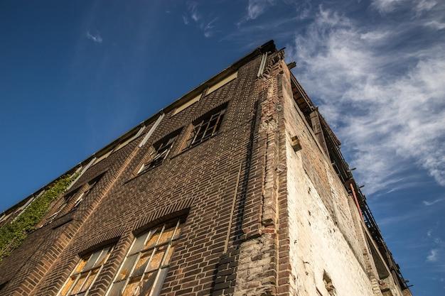 Lage hoek shot van een oud stenen gebouw onder de hemel met een paar wolken Gratis Foto