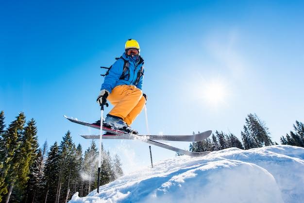 Lage hoek shot van een skiër in kleurrijke versnelling springen in de lucht tijdens het skiën op een helling Premium Foto