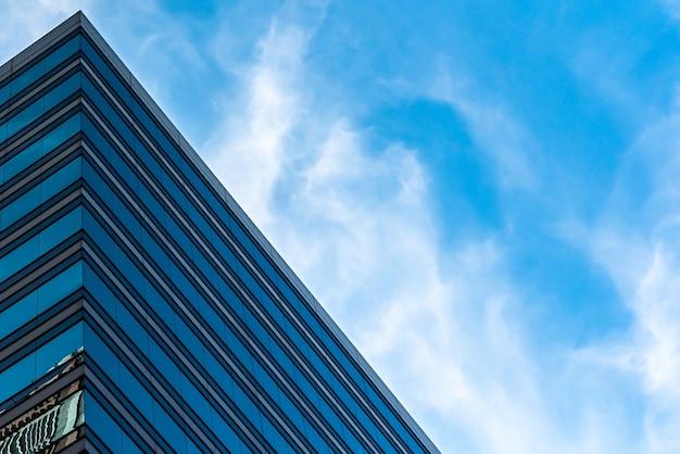 Lage hoek shot van hoge glazen gebouwen onder een bewolkte blauwe hemel Gratis Foto