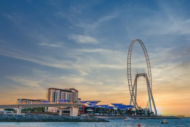 Lage hoek shot van modern design van een gebouw met een enorm reuzenrad op bluewaters island in dubai Gratis Foto