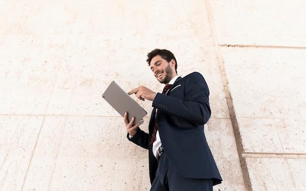 Lage hoek smiley man aan het werk op tablet pc Gratis Foto