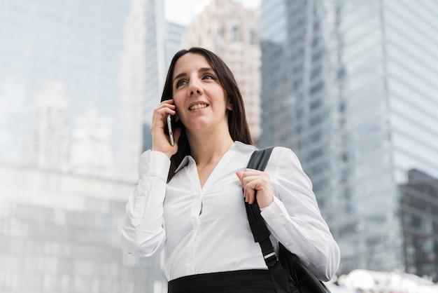 Lage hoek smiley vrouw praten aan de telefoon Gratis Foto