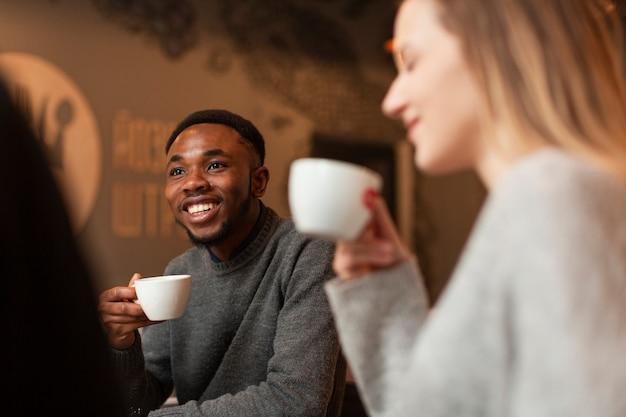 Lage hoek smileyvrienden die koffie drinken Gratis Foto