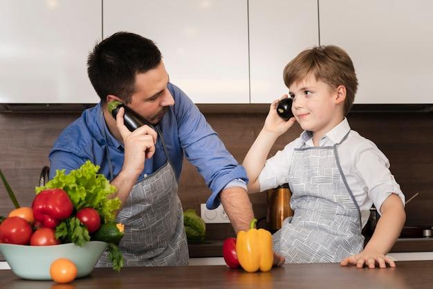 Lage hoek speelse vader en zoon in keuken Gratis Foto