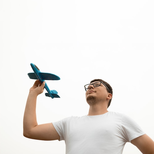 Lage hoek van jonge man met een vliegtuig Gratis Foto