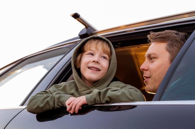 Lage hoek van vader en zoon in de auto tijdens een roadtrip Gratis Foto