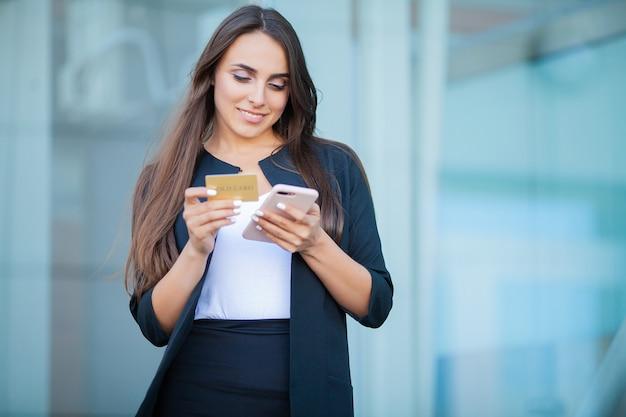 Lage hoek van verheugd meisje permanent in de luchthaven hal. hij gebruikt gold creditcard en mobiele telefoon voor het betalen Premium Foto