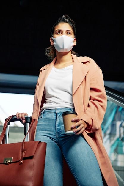 Lage hoek van vrouw met medisch masker en bagage op de luchthaven Gratis Foto