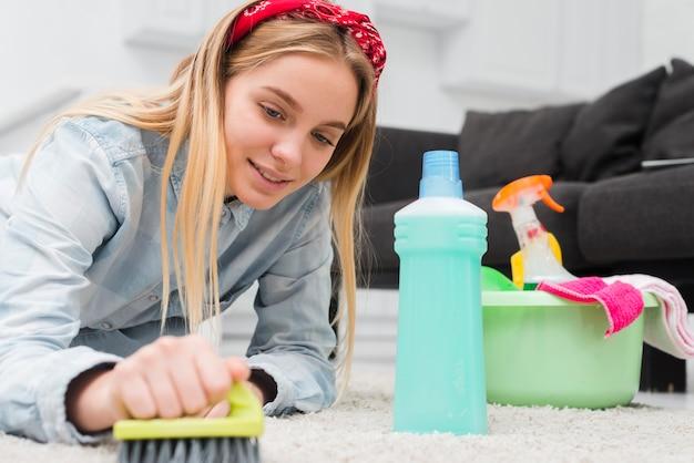 Lage hoek vrouw borstelen tapijt Gratis Foto