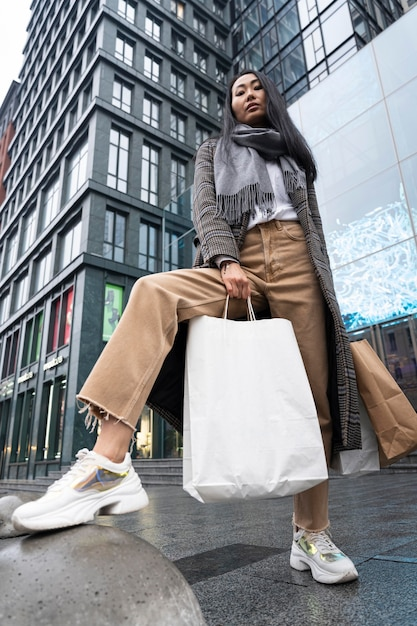 Lage hoek vrouw poseren met boodschappentassen Gratis Foto