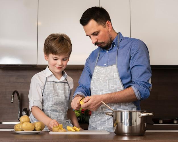 Lage hoek zoon bijwonende vader tijdens het koken Gratis Foto