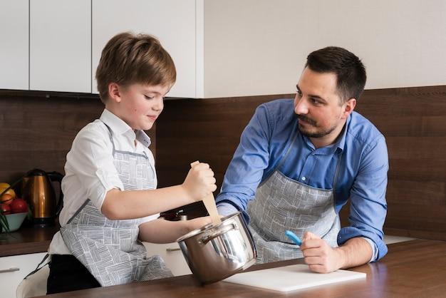 Lage hoek zoon en vader tijd koken Gratis Foto