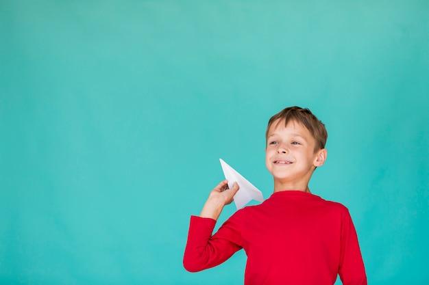 Lage hoekjongen die een document vliegtuig met exemplaarruimte werpt Gratis Foto