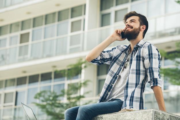 Lage hoekmening van de mens die goed nieuws op de telefoon deelt Gratis Foto