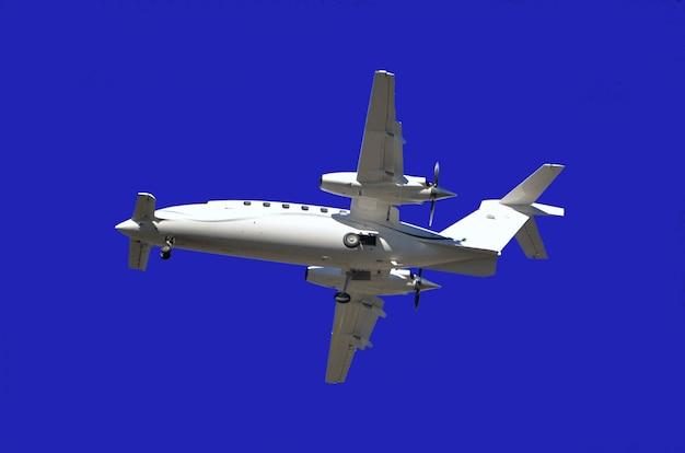 Lage hoekmening van een vliegtuig dat onder het zonlicht en een blauwe hemel overdag vliegt Gratis Foto